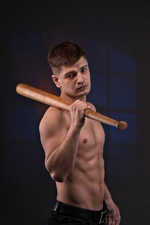 L'homme musculeux sur un fond noir avec la batte de baseball images libres de droits
