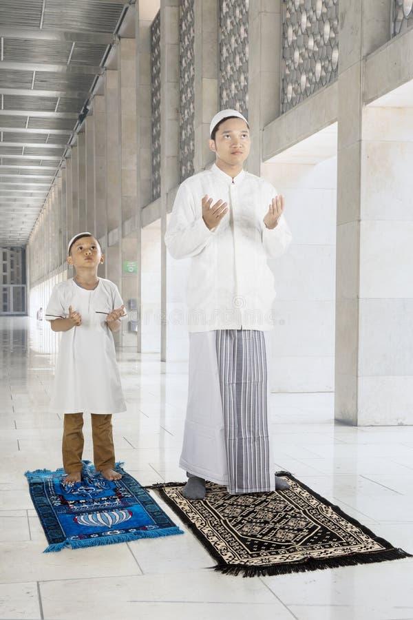 L'homme musulman avec son fils prie à un DIEU image stock