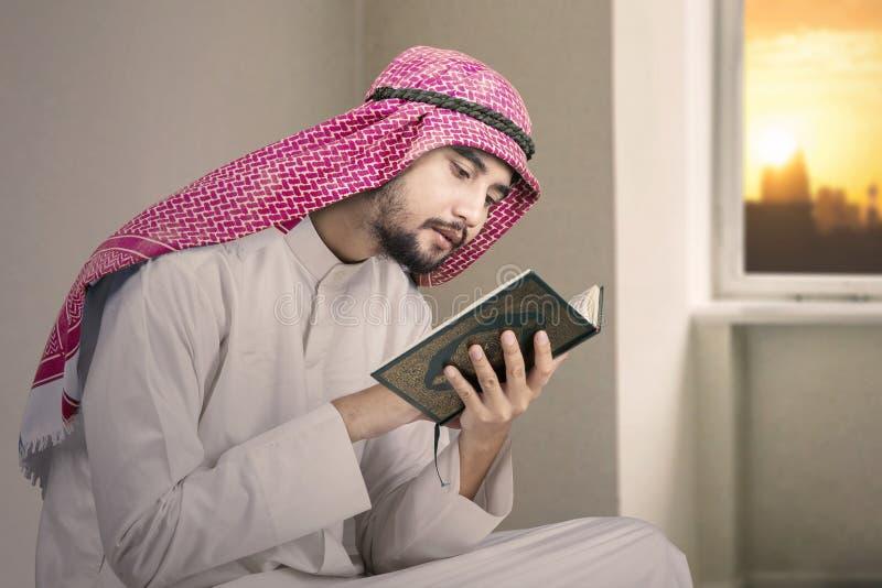 L'homme musulman dévot lit le Quran à la maison image libre de droits