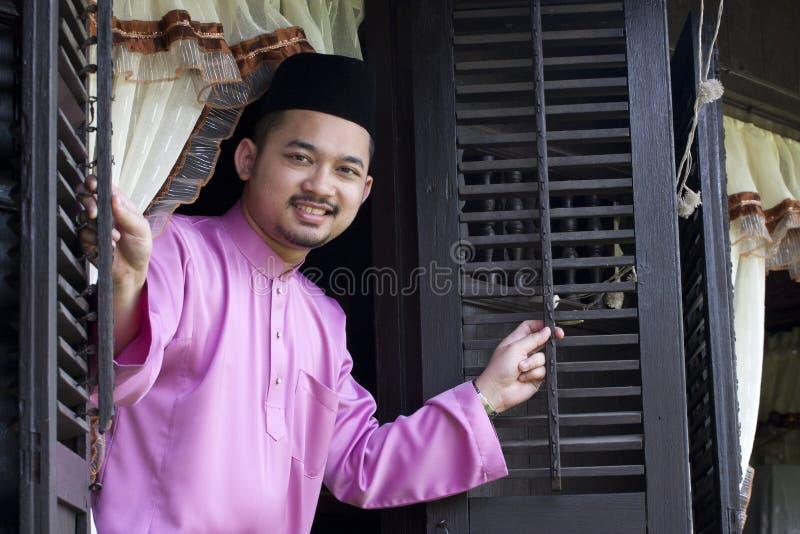 L'homme musulman malais ouvrent une fenêtre traditionnelle photographie stock