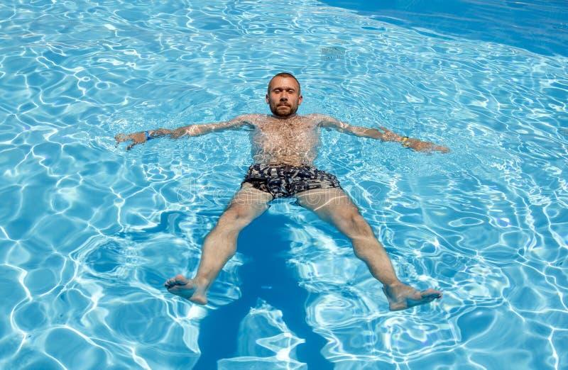 L'homme nage dans la piscine un jour ensoleill? lumineux photos libres de droits