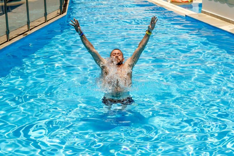 L'homme nage dans la piscine un jour ensoleill? lumineux photo libre de droits