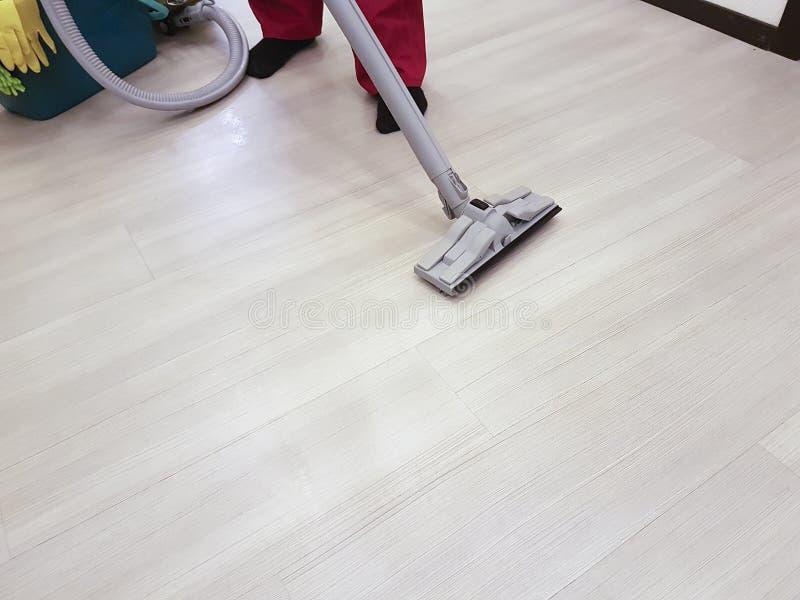 L'homme nettoie à l'aspirateur la scène d'équipement de nettoyage de plancher photos stock