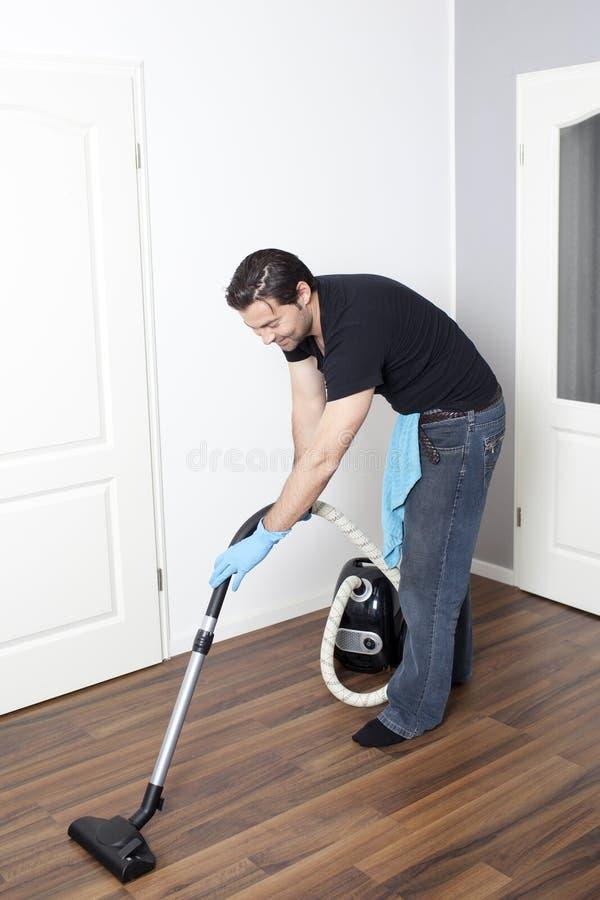 L'homme nettoie à l'aspirateur le plat photo stock
