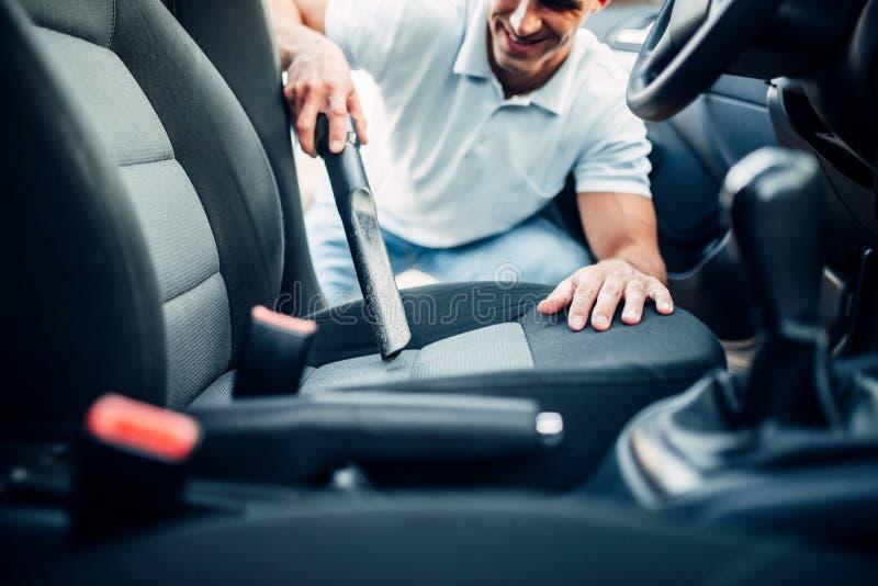 L'homme nettoie l'intérieur de voiture avec l'aspirateur image libre de droits