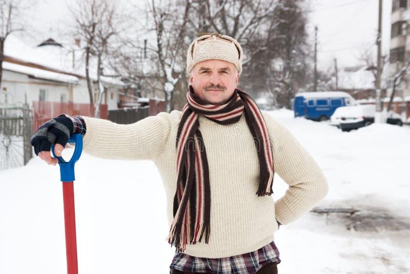 L'homme nettoie la neige photos stock