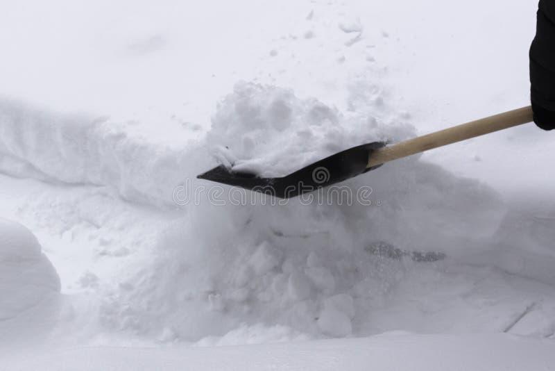 L'homme nettoie la neige avec une pelle i images stock