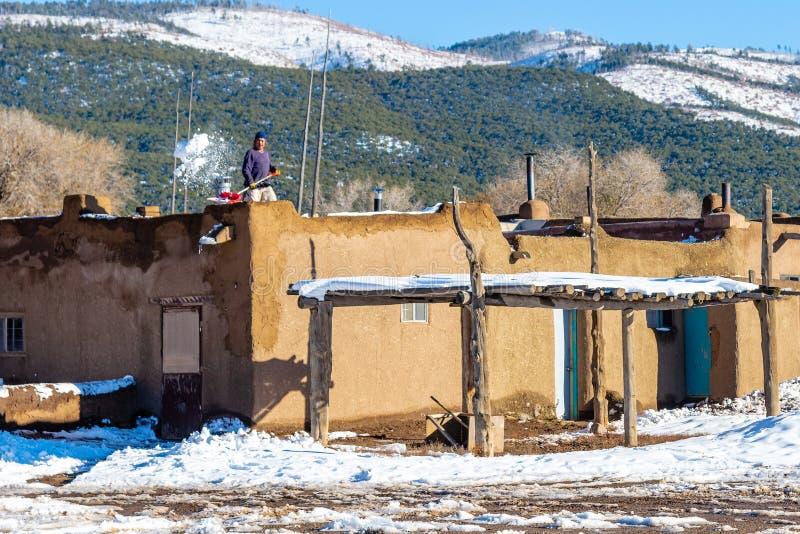 L'homme non identifié pelle la neige du toit d'une maison d'adobe dans le pueblo de Taos, un règlement de Natif américain sans in photo libre de droits