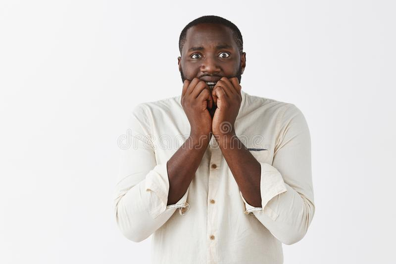 L'homme obtient à audition effrayée des histoires effrayantes d'ami Afro-américain attirant intense et nerveux effrayé avec le sh photos stock