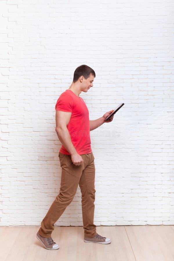 L'homme occasionnel à l'aide de la tablette occupée vont communication sociale de réseau photo stock
