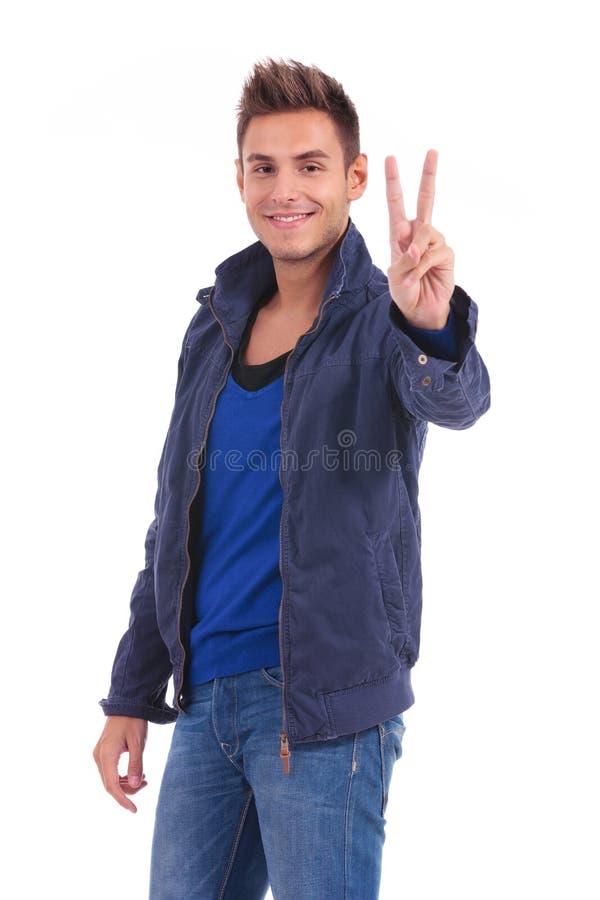 L'homme occasionnel dans une veste bleue fait le signe de main de victoire images stock
