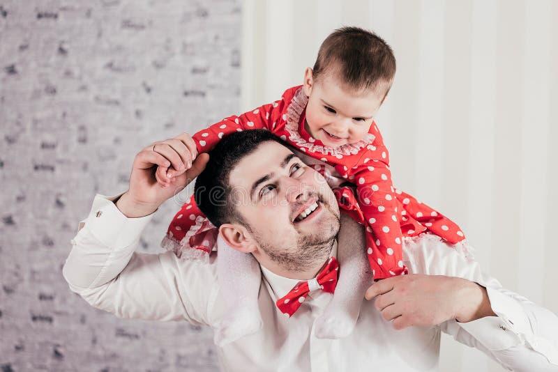 L'homme passe gaiement le temps avec la petite fille Le bébé avec du charme s'assied sur des épaules au père et rit gaiement images stock