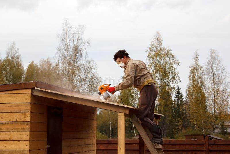 L'homme peint l'abri en bois avec le pistolet de pulvérisation photos stock