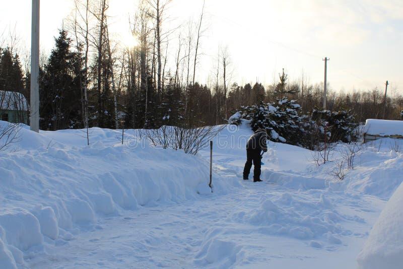 L'homme pelle la neige en dehors de sa maison images libres de droits