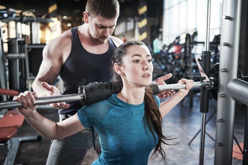 L'homme personnel d'entraîneur aide le travail de femme avec le barbell aux exercices accroupis dans le gymnase photos stock
