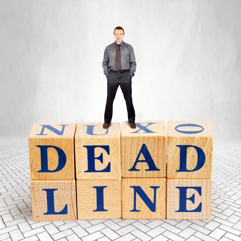 L'homme plein d'assurance se tient sur le dessus du tas des blocs en bois avec une date-butoir des textes photos libres de droits