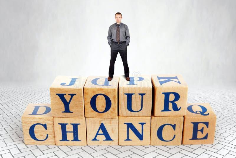 L'homme plein d'assurance tient sur le dessus du tas des blocs en bois avec un texte votre occasion photographie stock