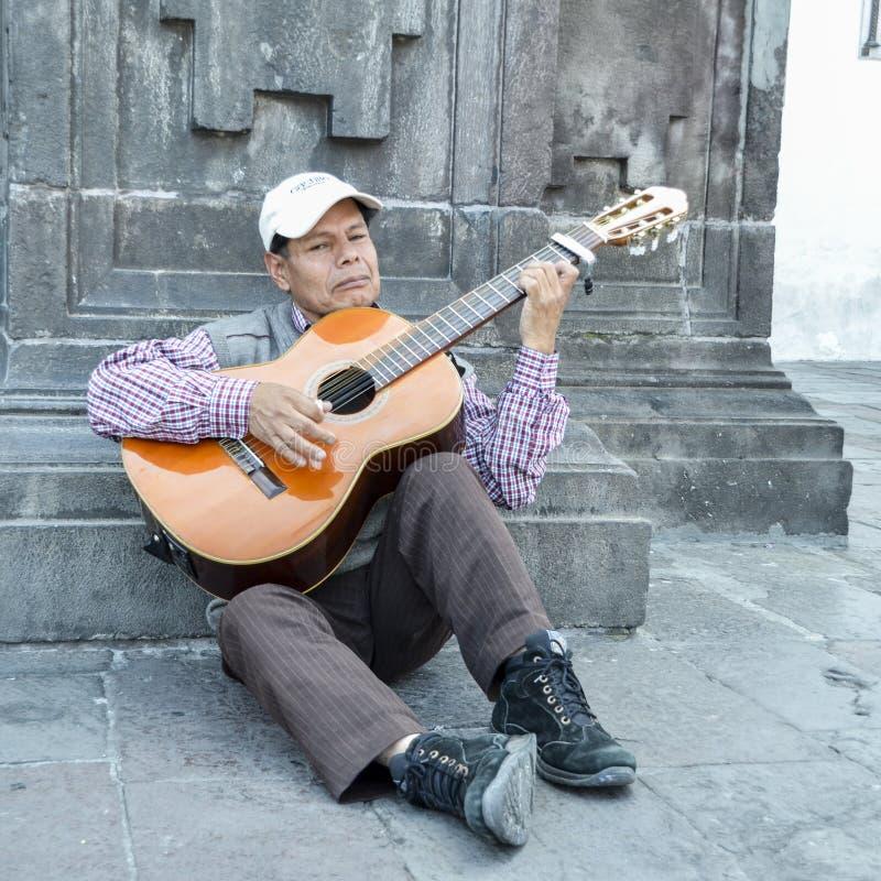 L'homme plus âgé équatorien local joue la guitare sur la rue image stock