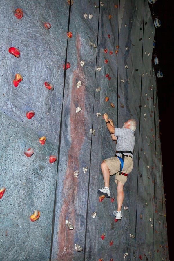 L'homme plus âgé avec les cheveux blancs et la barbe escalade un mur Simulat de roche photographie stock libre de droits
