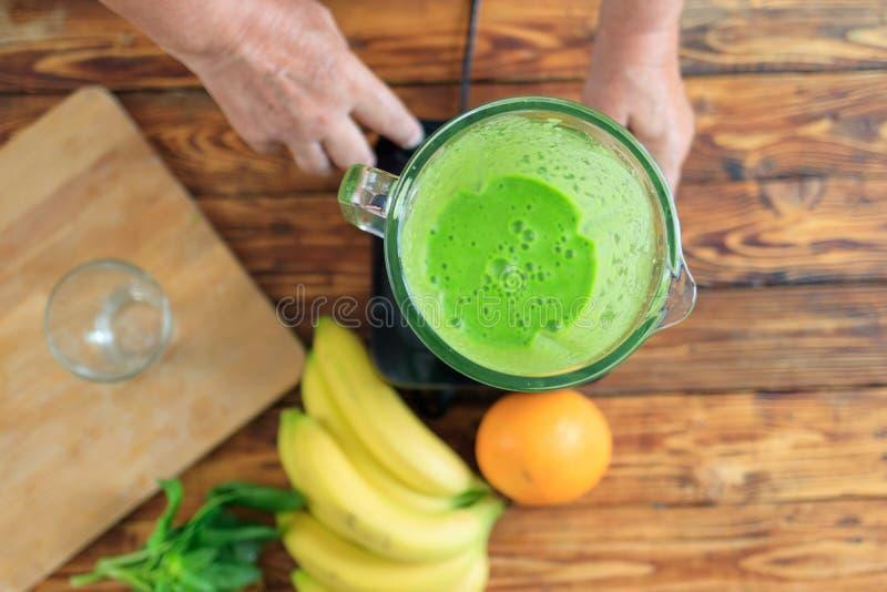 L'homme plus âgé fait le smoothie frais de jus de vitamine avec les épinards et la banane photo libre de droits