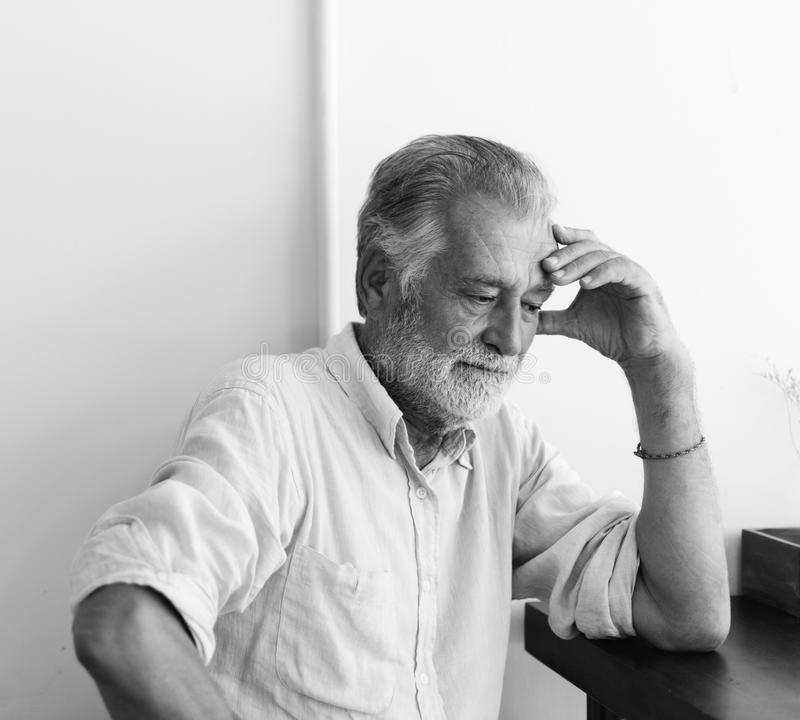 L'homme plus âgé s'assied pensivement images libres de droits