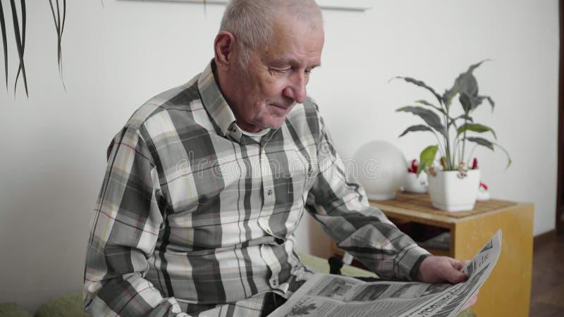 L'homme plus âgé s'assied une chaise et en lisant un journal dans un appartement moderne 4k images stock