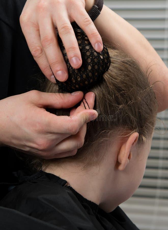 L'homme poignarde le petit pain de cheveux sous le filet goujons en métal, petite fille photographie stock libre de droits