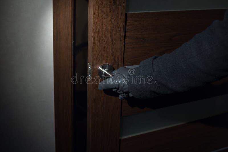 L'homme portant des gants ouvre la porte la nuit photos libres de droits