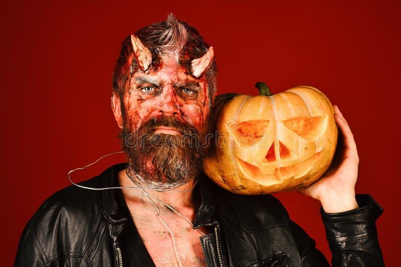 L'homme portant le maquillage effrayant tient le potiron sur le fond rouge ensanglanté photos stock