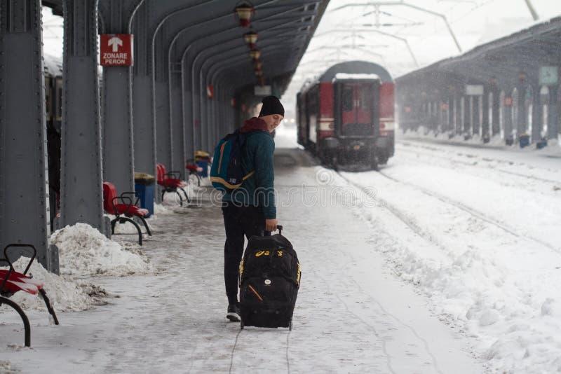 L'homme porte ses bagages sur la tempête de chute de neige importante image libre de droits