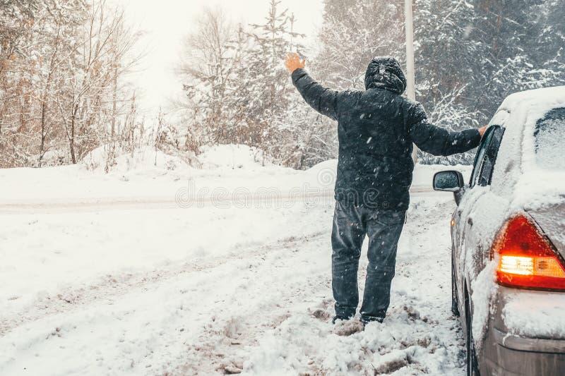 L'homme près de la voiture cassée sur la route d'hiver se lève main demandant l'aide, panne de transport sur la route de campagne images libres de droits