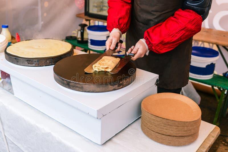 L'homme prépare des crêpes sur le fourneau Un homme enveloppe une crêpe bourrée Cuisson ? l'ext?rieur Le chef fait les crêpes cui photos libres de droits