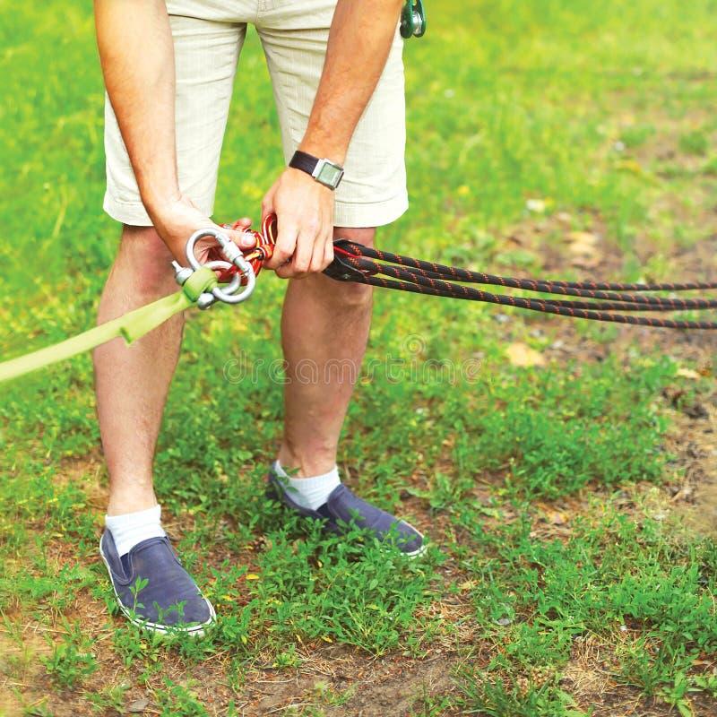 L'homme prépare des difficultés d'un équipement le carabiner sur la corde pour l'alpinisme photographie stock libre de droits
