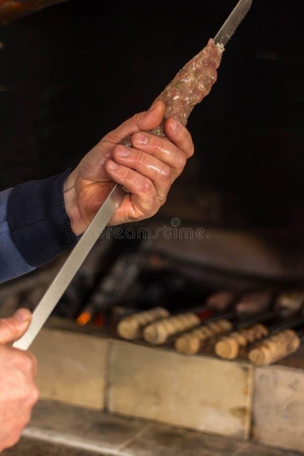 L'homme prépare la viande hachée pour le chiche-kebab et les côtelettes Dîner de famille Ensemble de photo image libre de droits