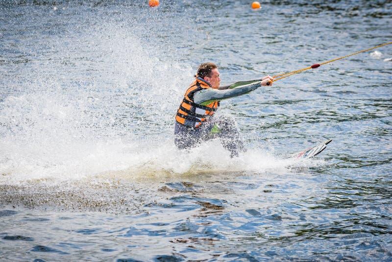 L'homme pratique le début de la glissière de planche de surf sur le wa images libres de droits