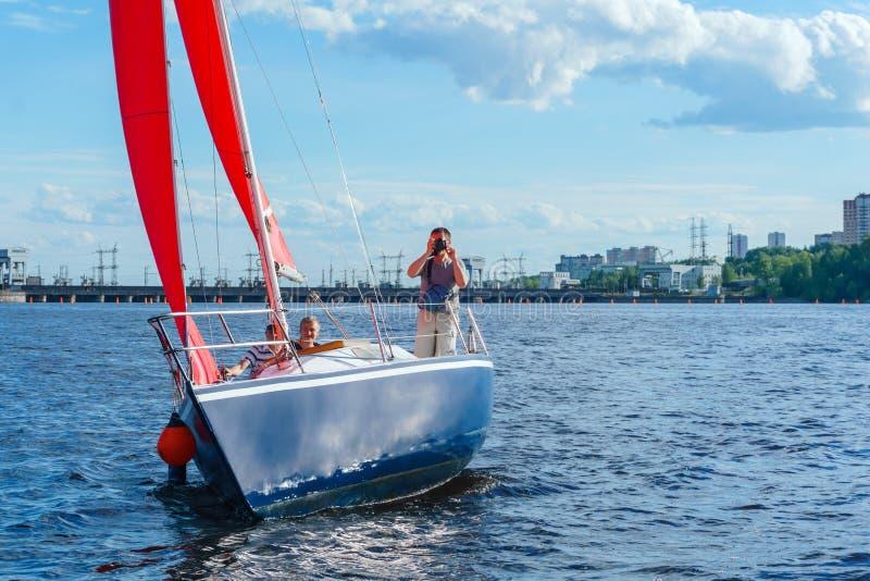 L'homme prend des photos du panneau du yacht sur le fond du réservoir de barrage photographie stock