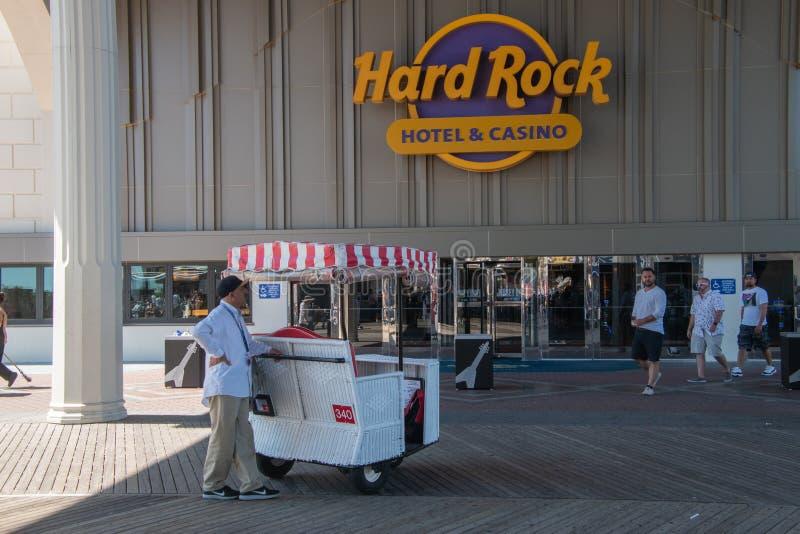 L'homme qui pousse une chaise de roulement célèbre attend un touriste pour demander un tour sur la promenade d'Atlantic City deva image libre de droits