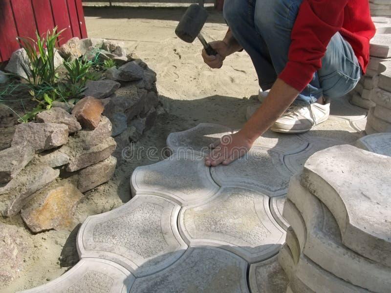 L'homme réalise le travail d'étendre les pavés avec un maillet sur le patio Beau fond de construction avec l'espace de copie, une photo libre de droits