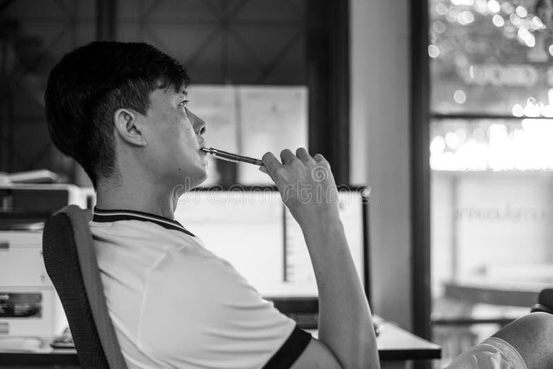 L'homme réfléchi asiatique de portrait de plan rapproché tient un crayon et la pensée dur sur son travail avec l'écran lumineux b image libre de droits