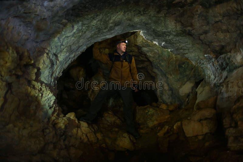 L'homme regarde autour, se tenant dans une caverne de karst photo libre de droits