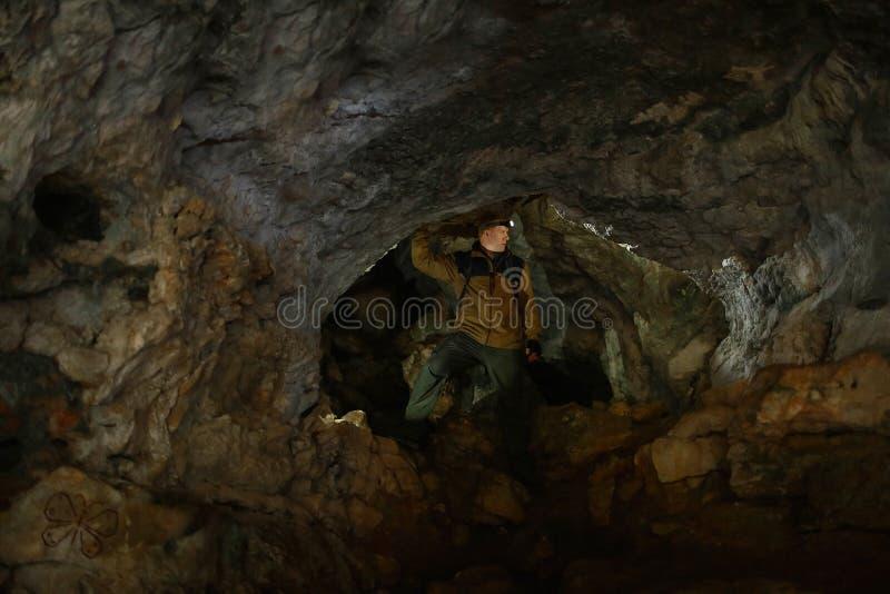 L'homme regarde autour, se tenant dans une caverne de karst image stock