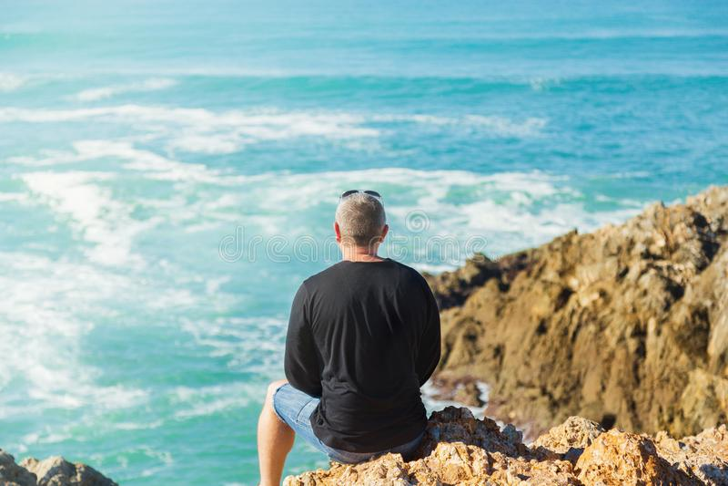 L'homme regarde la mer des roches image stock