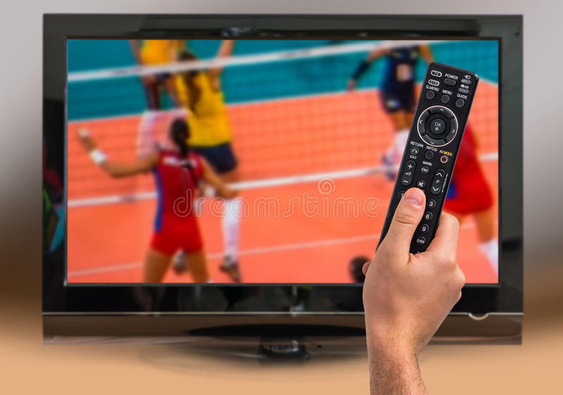 L'homme regarde la rencontre de volleyball à la TV image libre de droits