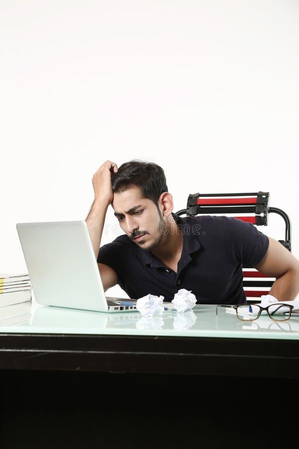 L'homme regarde le travail sur l'ordinateur portable avec le papier de rebut sur la table photo stock
