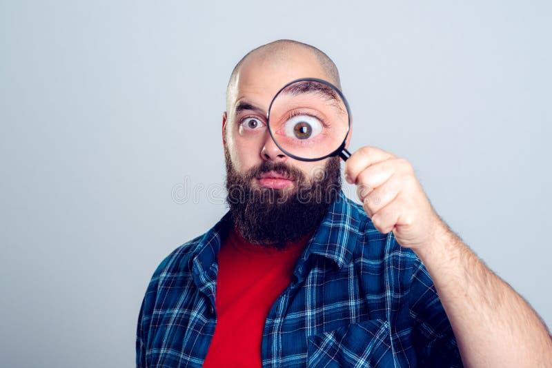 L'homme regarde par la loupe images stock