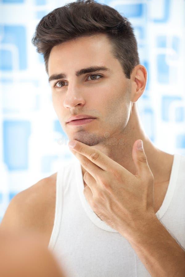 L'homme regarde sa barbe photo libre de droits