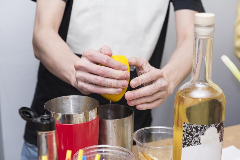 L'homme remet à des écrasements un citron dans un dispositif trembleur, préparant un cocktail, des hommes image stock