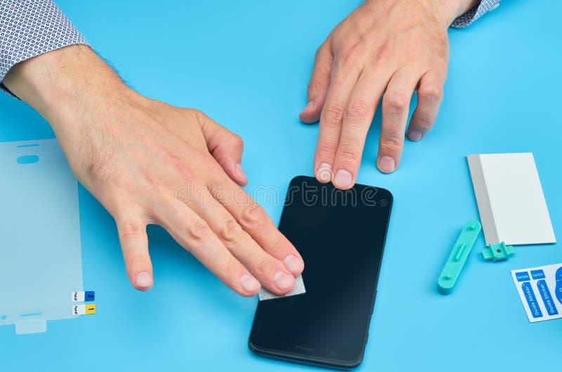 L'homme remplaçant le protecteur cassé d'écran de verre trempé pour le smartphone image stock