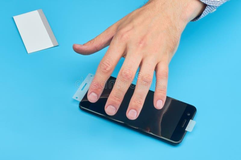L'homme remplaçant le protecteur cassé d'écran de verre trempé pour le smartphone photos stock