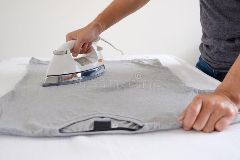 L'homme repasse le T-shirt images stock